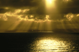 sunrays shining through dark clouds onto sea, phillip island, vic